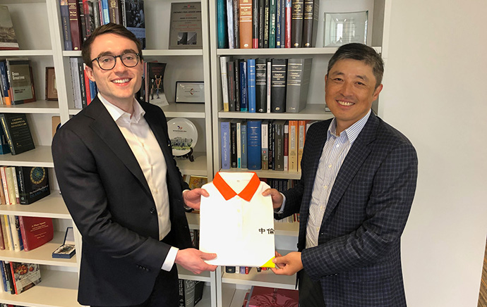 Law student James Flynn receives a gift of a Zhong Lun Law Firm golf shirt, ahead of his placement in Shanghai this summer, from alumnus and award donor, Scott Guan, SJD 2003.