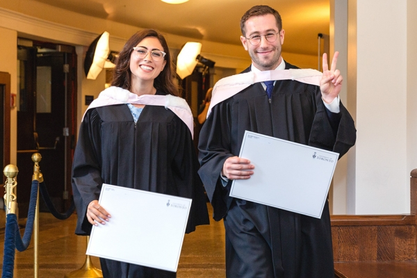 Two law grads in Con Hall who picked up their degrees