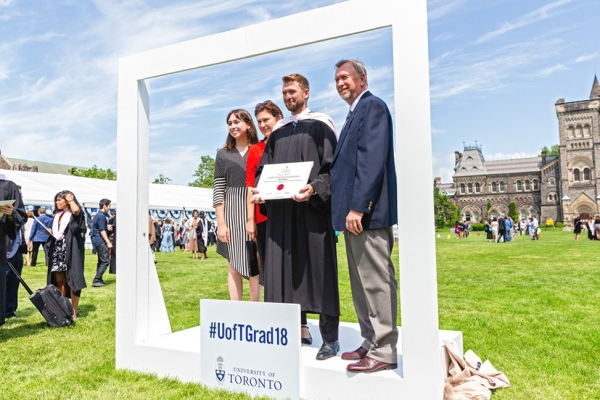 Law grad with family in the Instagram frame by Convocation Plaza