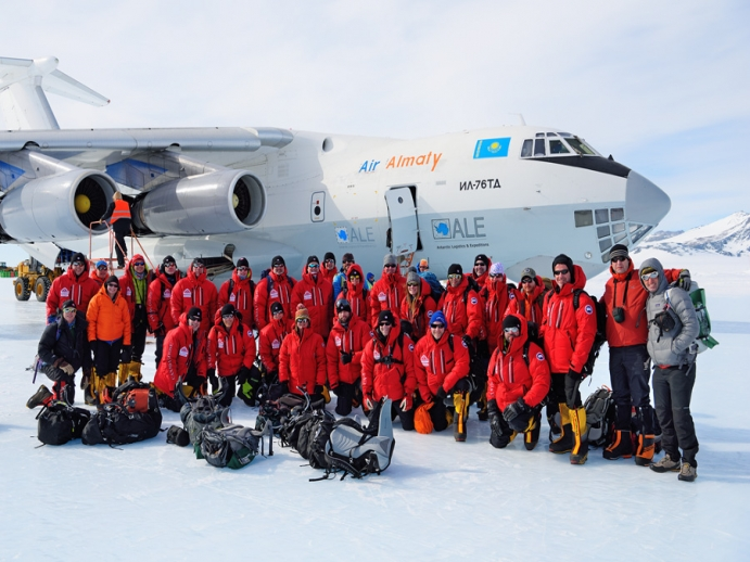 Expedition team in front of military jet on Antarctica