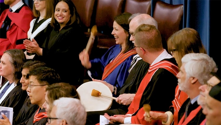 Amanda Carling, pictured centre, beats a drum to honour Indigenous grads at U of T's spring convocation (photo by Johnny Guatto)