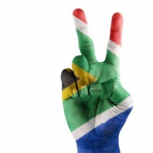 South African flag painted on a hand depicting the V for victory sign