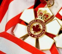 close up shot of order of canada medallion sitting on ribbon