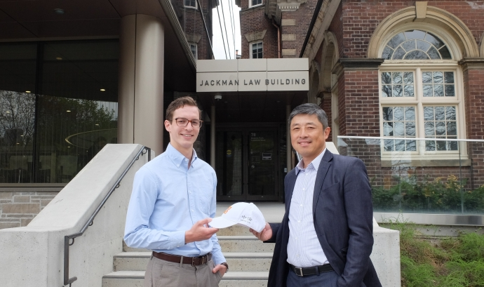 Law student D'Arcy White receives a law firm hat from alumnus Dr. Scott Guan in front of the doors to the Jackman Law Building