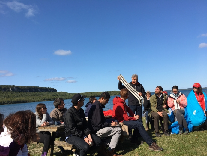 Law students attend the Indigenous Law in Context course at Cape Croker reserve, here sitting by Georgian Bay as faculty teach
