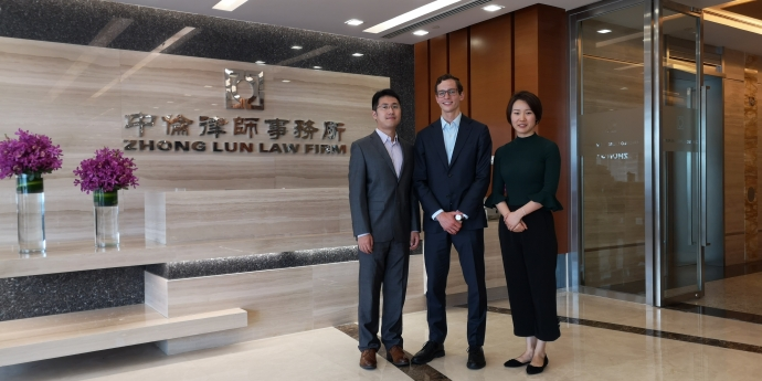 Law student D'Arcy White, centre, with colleagues from Zhong Lun Law firm, by the firm's front door in the lobby