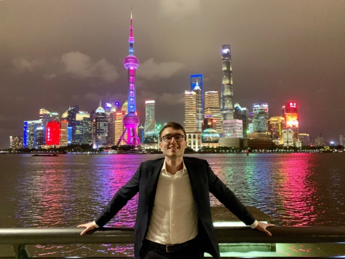 law student james flynn with night time Shanghai skyline behind him