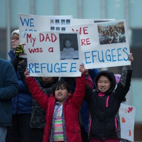 children with pro-refugee signs at a protest